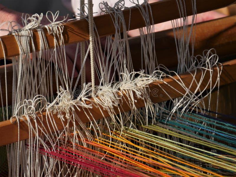 Het detail van de draden van een handweefgetouw, de rug past en handen in royalty-vrije stock afbeelding