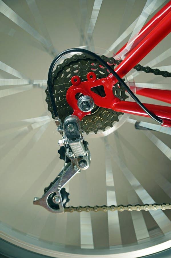 Het detail van de fiets Het achterwiel van de rode fiets met derailleur, het wiel roteert stock foto