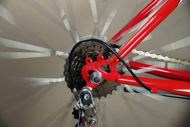 Het detail van de fiets Het achterwiel van de rode fiets met derailleur, het wiel roteert royalty-vrije stock fotografie