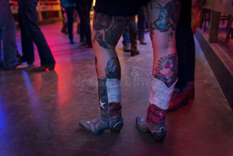 Het detail van de laarzen en tattoed benen van een jonge vrouw in Gebroken sprak disco in Austin, Texas stock afbeelding