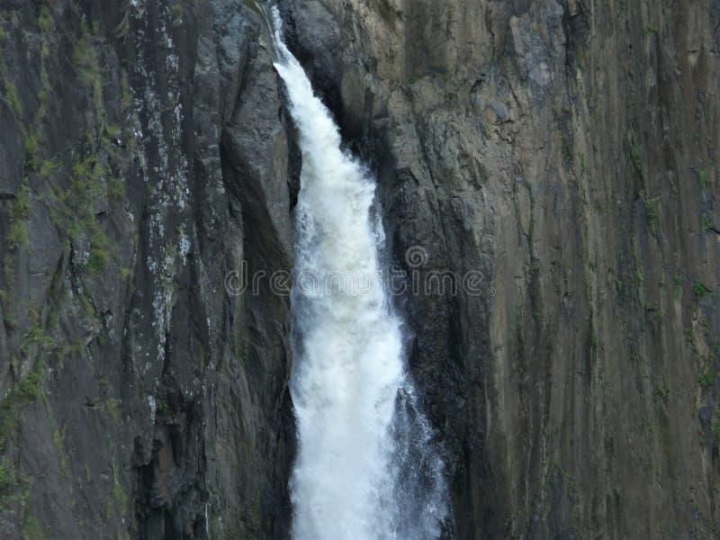 Het detail van een kleine waterval, het water verplettert onderaan de rotsen stock afbeeldingen