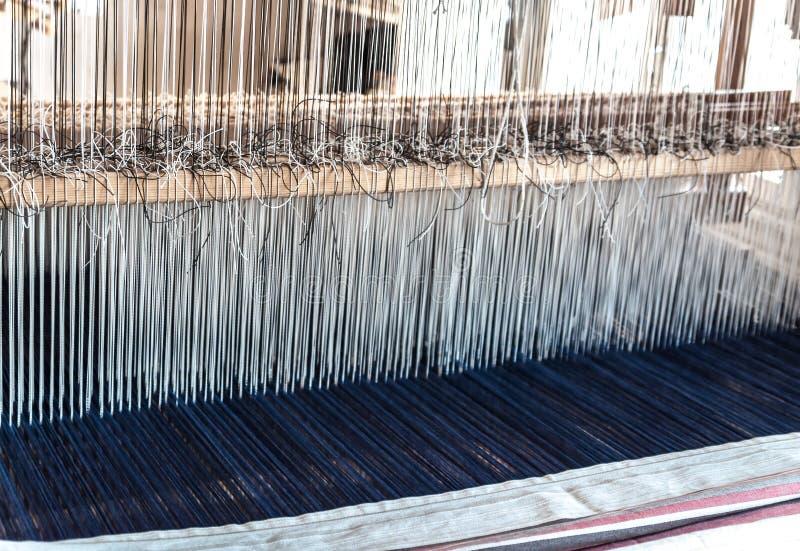 Het detail van een oud traditioneel uitstekend wevend weefgetouw met vele katoenen koorden bond aan een houten kader als beroeps stock fotografie