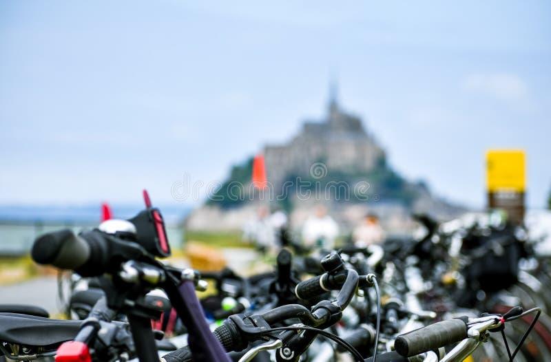 Het detail van geparkeerde fietsen, met defocused silhouet van Mont Saint Michel, Frankrijk stock fotografie