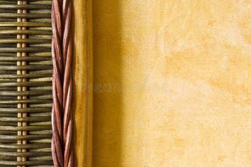 Het detail van het bamboe tegen gele muur stock fotografie