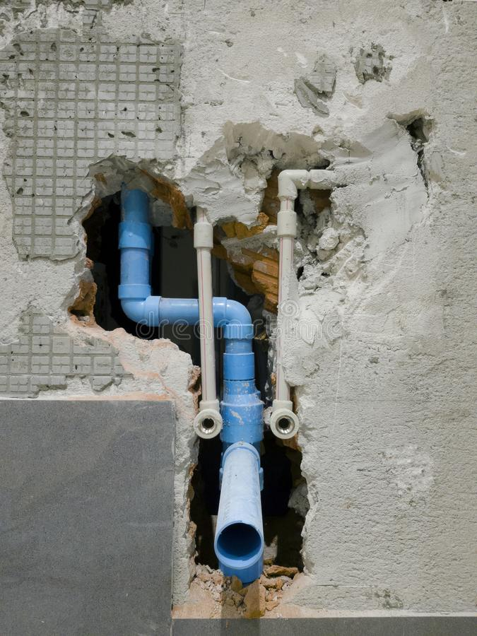 Het detail van metaalwaterpijpen en de de rioolbuis blauwe kleur van pvc verschijnen in gebroken badkamersmuur, in aanbouw flatpl stock foto's