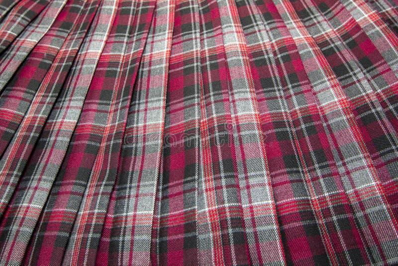 Het detail van nieuwe manierplaid plooide rok: rood, kastanjebruin, grijs eenvormig de stoffenkatoen van de geruit Schots wollen  royalty-vrije stock afbeelding
