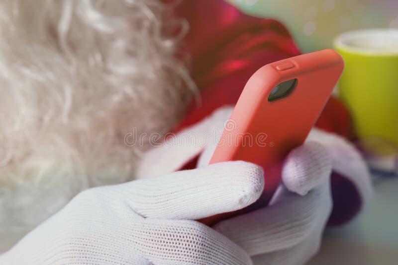 Het detail van Santa Claus overhandigt bewaarceltelefoon en het controleren van sociale media stock foto