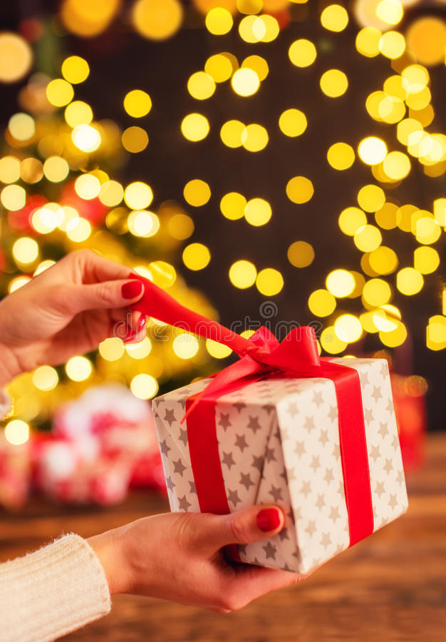 Het detail van vrouw overhandigt het openen Kerstmisgift stock afbeelding