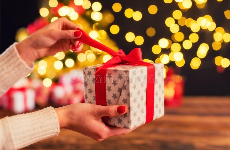 Het detail van vrouw overhandigt het openen Kerstmisgift stock foto