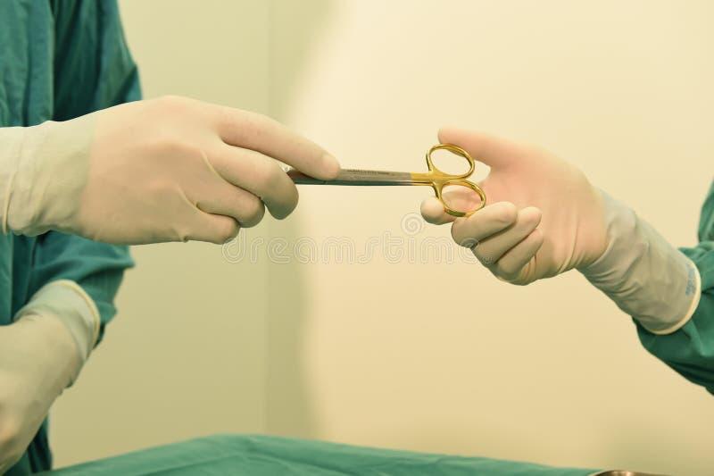 Het detailschot van steralized chirurgieinstrumenten met een hand grijpend een hulpmiddel royalty-vrije stock fotografie