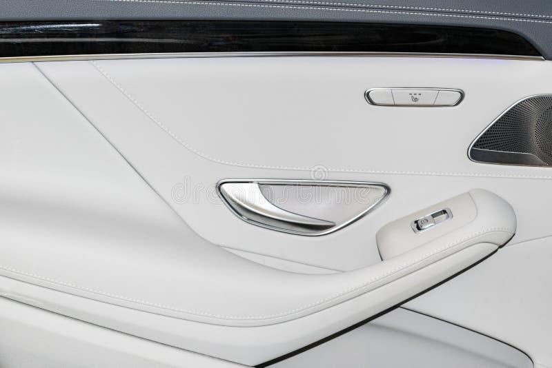 Het deurhandvat met Machtszetel en het venster controleren knopen van een luxepersonenauto Wit leerbinnenland van de luxe moderne royalty-vrije stock foto's