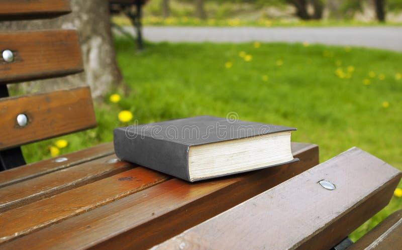 Het dichte boek in de grijze dekking ligt op een parkbank stock afbeeldingen