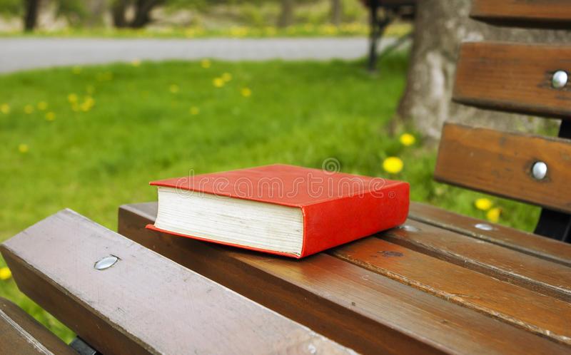 Het dichte boek in de rode dekking ligt op een parkbank stock fotografie