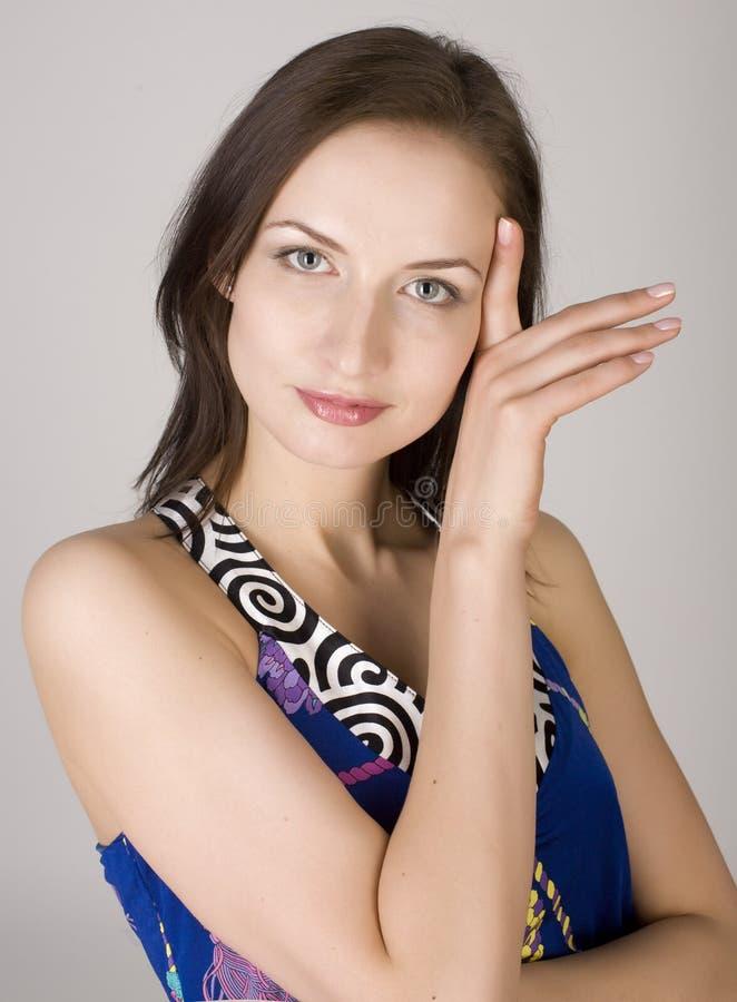 Het dichte omhooggaande portret van de voorraadfoto van het mooie jonge vrouwelijke model stellen tegen grijze achtergrond stock foto