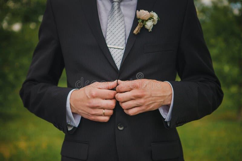 Het dichtknopen van een jasje overhandigt dicht omhoog De modieuze mens in kostuum maakt knopen vast en maakt zijn jasje recht He royalty-vrije stock afbeeldingen