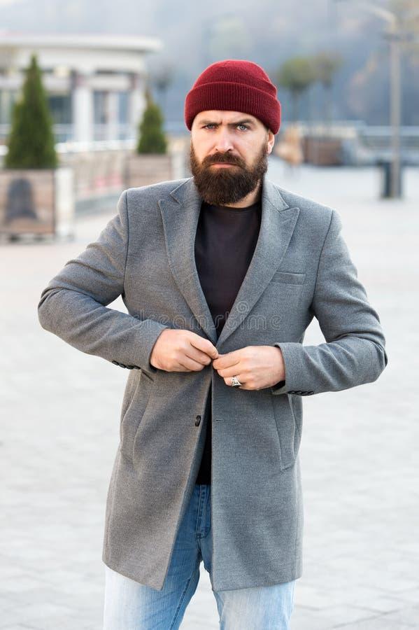 Het dichtknopen van zijn jasje Hipsteruitrusting en hoedentoebehoren Modieuze toevallige uitrustingslentetijd Menswear en manneli stock fotografie