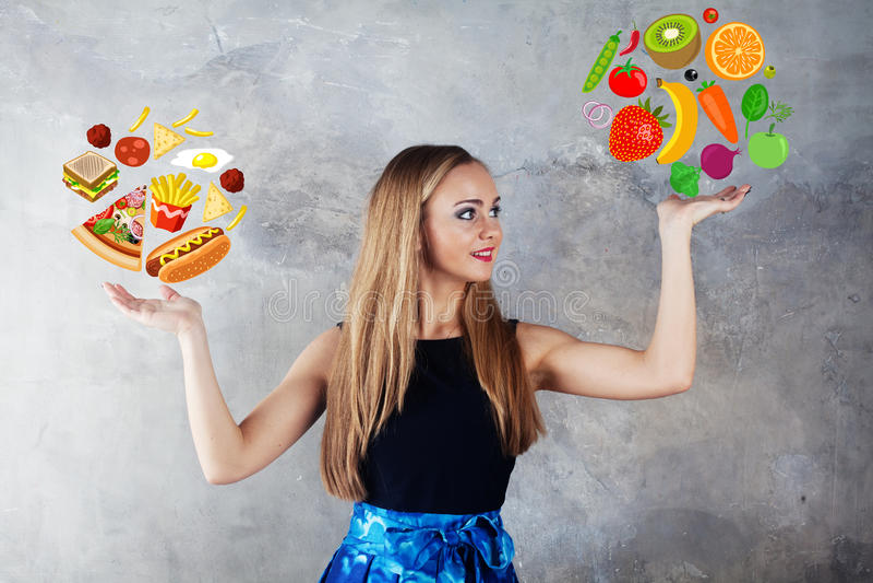 Het dieetmeisje kiest tussen voedsel royalty-vrije stock fotografie