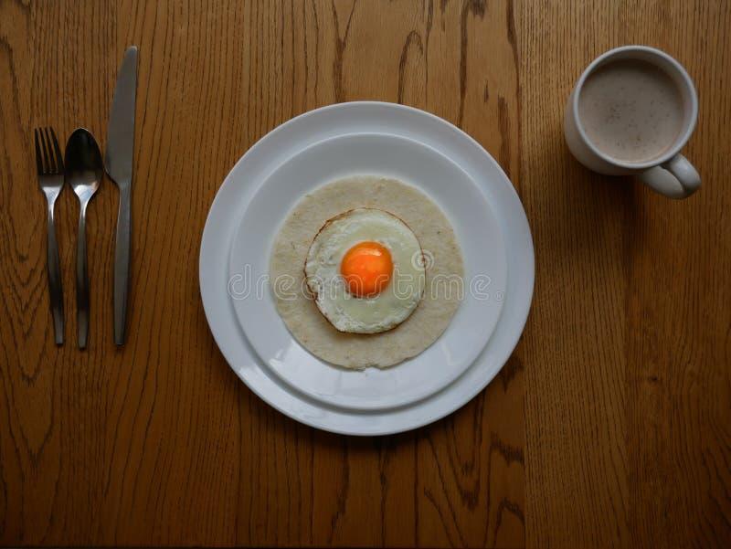 Het dienen van een gebraden ei met oranje dooier over een graancake diende voor het dienen van ontbijt op een witte ronde plaat o stock afbeeldingen
