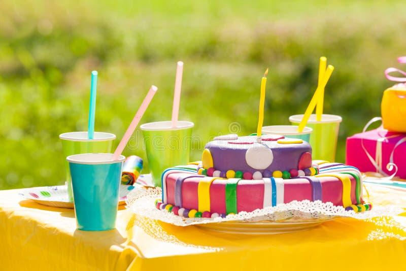Het dienen van feestelijke lijst met verjaardagscake stock fotografie