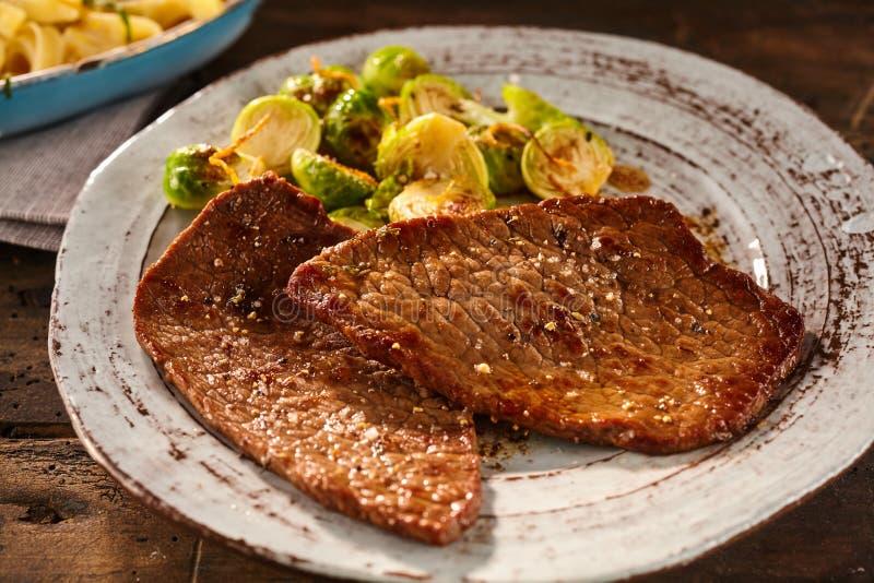 Het dienen van gemarineerd en gekookt miniem lapje vlees met veggies stock afbeelding
