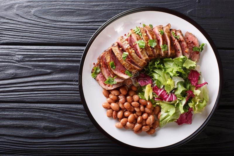 Het dienen van geroosterd rundvleeslapje vlees met verse salade en bonenclose-up o stock afbeeldingen