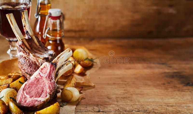 Het dienen van geroosterde lamskoteletten met groenten stock foto