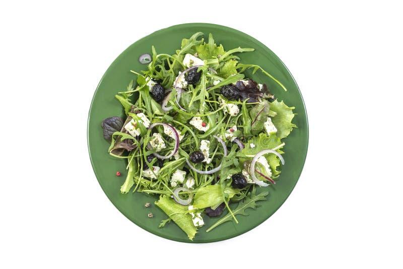 Het dienen van verse Griekse salade met bladgreens, kruiden, arugulan feta, olijven, feta en olijven op een groene witte olate, stock fotografie