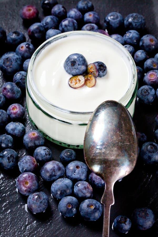 Het dienen van Yoghurt met Gehele Verse Bosbessen en Havermeel op Oude Rustieke Lijst stock afbeeldingen