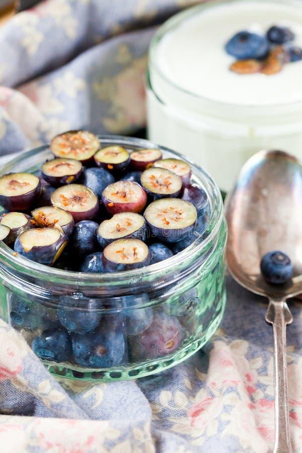 Het dienen van Yoghurt met Gehele Verse Bosbessen en Havermeel op Oude Rustieke Lijst stock afbeelding