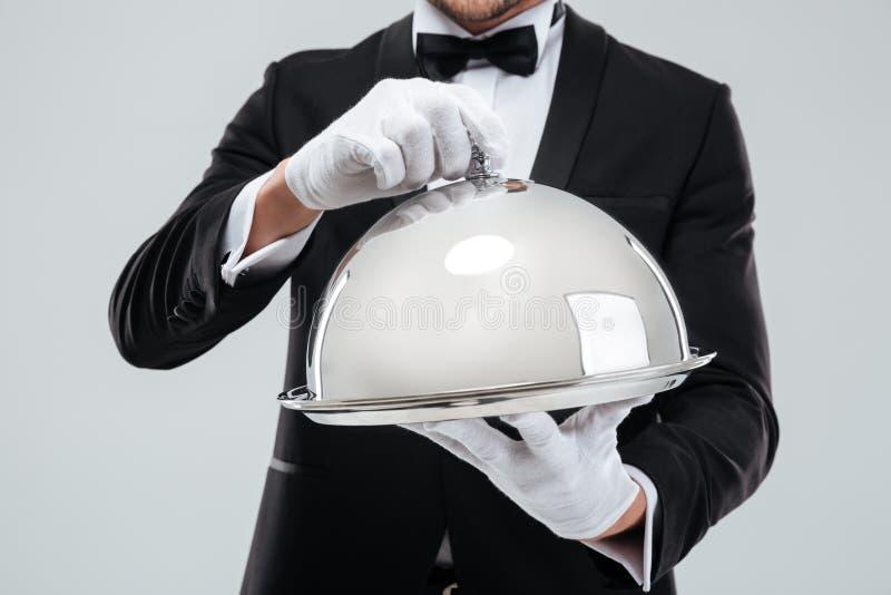 Het dienende dienblad met glazen kap holded door butlers indient handschoenen royalty-vrije stock foto