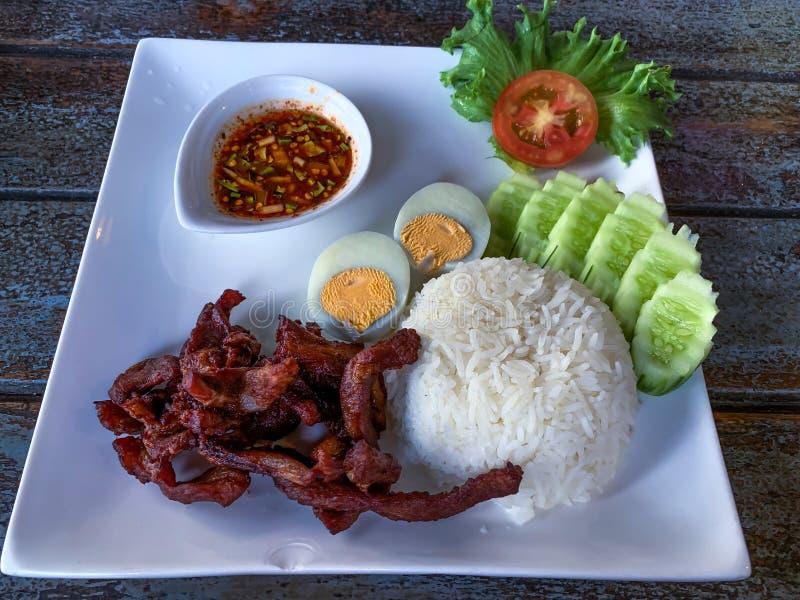 Het diepe die varkensvlees in witte plaat in brand werd wordt gestoken werd gediend met rijst, gekookte ei en het koelen saus royalty-vrije stock foto's