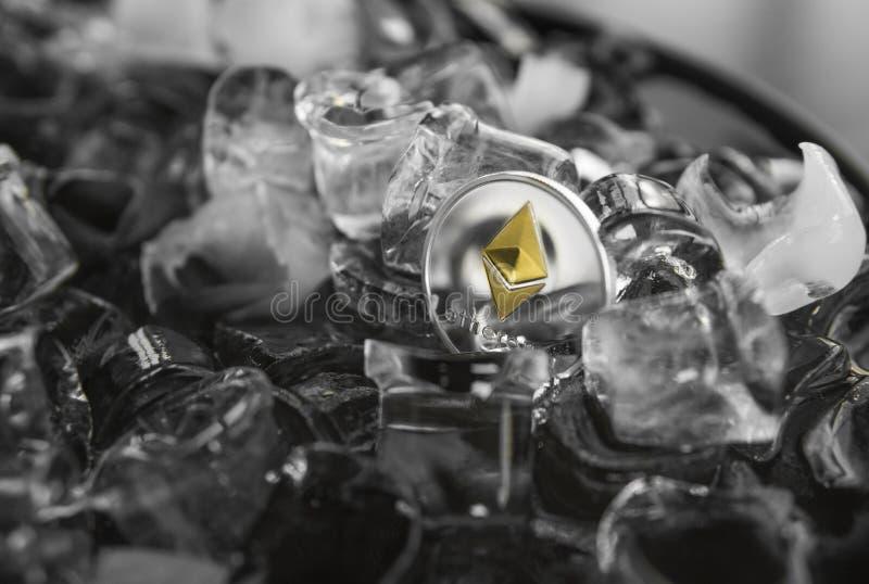 Het digitale crypto muntstuk van Ethereum van het munt fysieke metaal gouden op ijsachtergrond Blockchainmijnbouw Digitaal geld e stock foto
