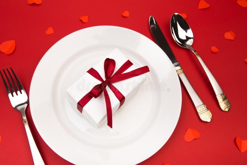 Het diner van de valentijnskaartendag met lijstplaats die die met gift plaatsen, met harten op rode achtergrond wordt verfraaid M royalty-vrije stock afbeelding