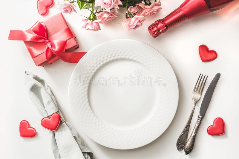 Het diner van de valentijnskaartendag met lijstplaats die met rode gift, een fles plaatsen champagne, roze rozen, harten met tafe stock foto