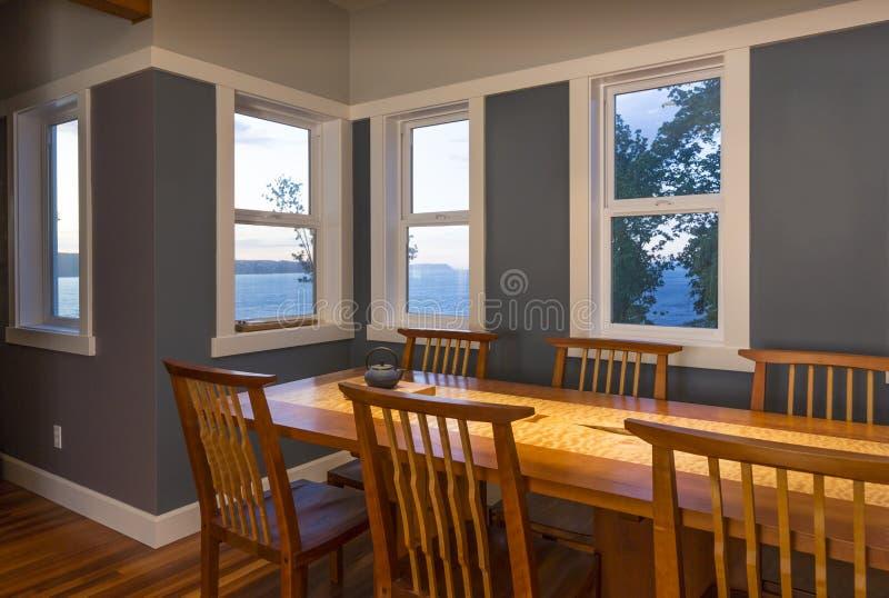 Het dineren gebied met houten lijst en stoelen en meningsvensters in eigentijds huisbinnenland voor de betere inkomstklasse royalty-vrije stock fotografie