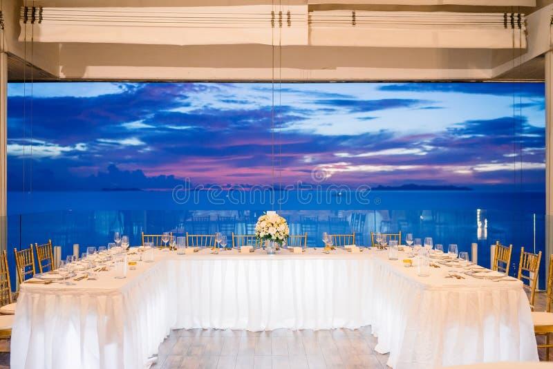 Het dinerlijst die van de huwelijksontvangst tijdens zonsondergang met oceaanmeningsachtergrond plaatsen royalty-vrije stock foto's