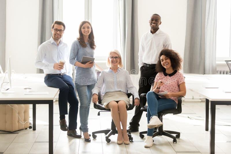 Het diverse gelukkige de groep van personeelswerknemers stellen voor portret in bureau stock afbeelding