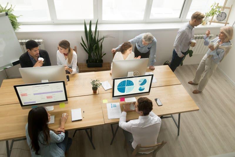 Het diverse jonge en hogere beambten samenwerken die, t spreken stock afbeeldingen