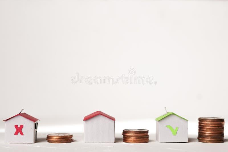 Het document huisvest dichtbij muntstukstapels om huiswaarde te vertegenwoordigen stock afbeelding
