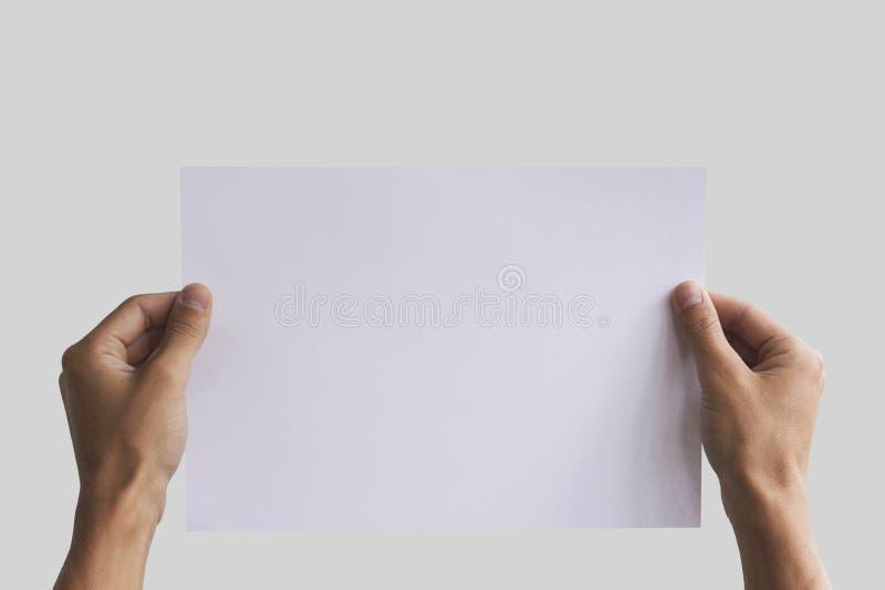 Het document van de handholding A4 in de hand Pamfletpresentatie De mens van de pamflethand De mens toont compensatiedocument Bla stock foto