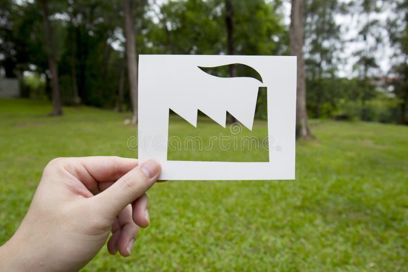 Het document van de handholding in fabrieksvorm wordt gesneden op groen gras dat stock foto's