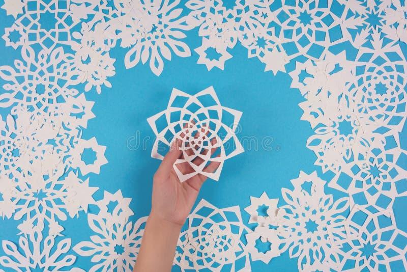 Het document van de handholding sneeuwvlok op blauwe achtergrond Hoogste mening De decoratie van Kerstmis stock afbeeldingen