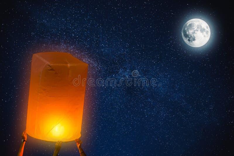 Het Document van de mensenversie Brandlamp die over de volle maan van de nachthemel toenemen stock fotografie
