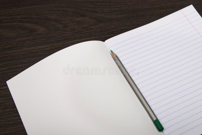Het document van het schoolnotitieboekje oranje tellers Notitieboekje in lijn en potlood open notitieboekje op een bruine achterg stock fotografie