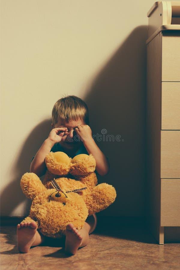Het doen schrikken jongen schreeuwen in hoek met stuk speelgoed draagt royalty-vrije stock afbeelding