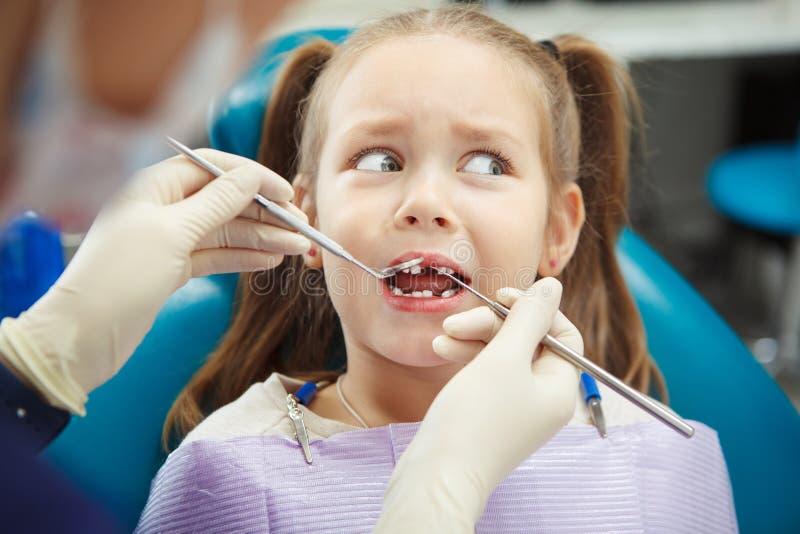 Het doen schrikken kind zit bij tandartsstoel met open mond royalty-vrije stock afbeelding