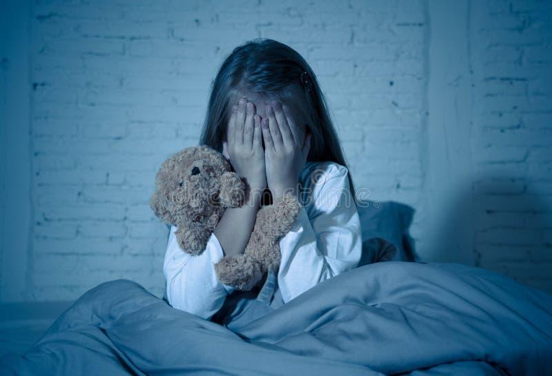 Het doen schrikken meisje die gezicht behandelen met dient vrees in duisternis bij nacht in stock foto