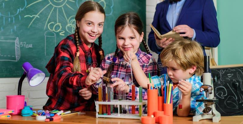 het doen van experimenten met vloeistoffen in chemielaboratorium Kinderen die wetenschapsexperimenten maken Onderwijs Terug naar  royalty-vrije stock afbeeldingen