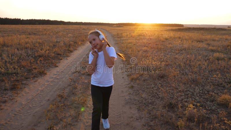 het doen van sporten die bij zonsondergang buiten stad aanstoten het jonge meisje in een witte T-shirttreinen bij zonsondergang e stock foto's
