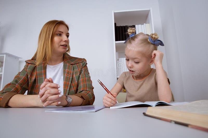 Het doen van taken en het bestuderen van concept Babysitter met meisje het schrijven thuiswerk stock afbeeldingen